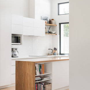 Contemporary l-shaped kitchen in Other with flat-panel cabinets, white cabinets, wood benchtops, white splashback, light hardwood floors, with island, beige floor, brown benchtop and vaulted.