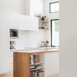 Стильный дизайн: угловая кухня в современном стиле с плоскими фасадами, белыми фасадами, деревянной столешницей, белым фартуком, светлым паркетным полом, островом, бежевым полом, коричневой столешницей и сводчатым потолком - последний тренд