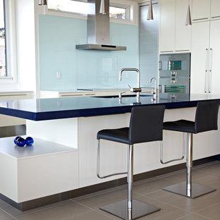 Ejemplo de cocina moderna con electrodomésticos con paneles, armarios con paneles lisos, puertas de armario blancas, salpicadero azul, salpicadero de vidrio templado y encimeras azules