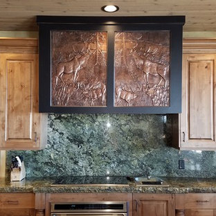 This is an example of an arts and crafts kitchen in Other with raised-panel cabinets, medium wood cabinets, granite benchtops, green splashback, stone slab splashback and green benchtop.