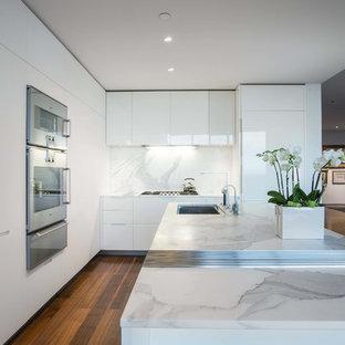 ソルトレイクシティの広いモダンスタイルのおしゃれなキッチン (アンダーカウンターシンク、フラットパネル扉のキャビネット、白いキャビネット、大理石カウンター、白いキッチンパネル、大理石のキッチンパネル、パネルと同色の調理設備、無垢フローリング、茶色い床) の写真