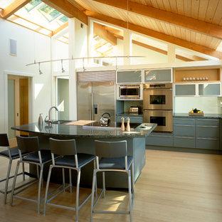 バンクーバーの大きいラスティックスタイルのおしゃれなキッチン (ダブルシンク、フラットパネル扉のキャビネット、青いキャビネット、淡色無垢フローリング、ターコイズのキッチンカウンター) の写真