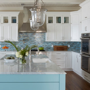 This is an example of a large beach style l-shaped open plan kitchen in Jacksonville with a farmhouse sink, recessed-panel cabinets, turquoise cabinets, quartzite benchtops, blue splashback, glass tile splashback, stainless steel appliances, medium hardwood floors, with island and brown floor.