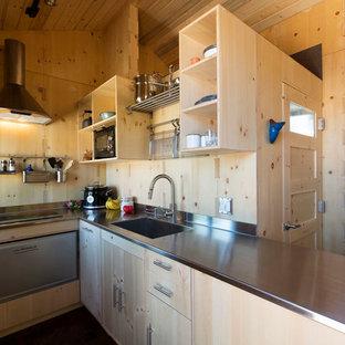 Kleine, Offene Moderne Küche in L-Form mit flächenbündigen Schrankfronten, hellen Holzschränken, Edelstahl-Arbeitsplatte, dunklem Holzboden, Unterbauwaschbecken, Küchenrückwand in Beige, Rückwand aus Holz, Küchengeräten aus Edelstahl, Halbinsel und braunem Boden in Albuquerque