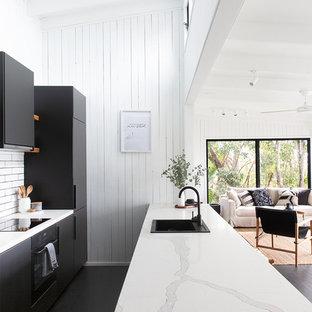 サンシャインコーストのビーチスタイルのおしゃれなキッチン (ドロップインシンク、フラットパネル扉のキャビネット、黒いキャビネット、白いキッチンパネル、黒い調理設備、塗装フローリング、黒い床、白いキッチンカウンター) の写真