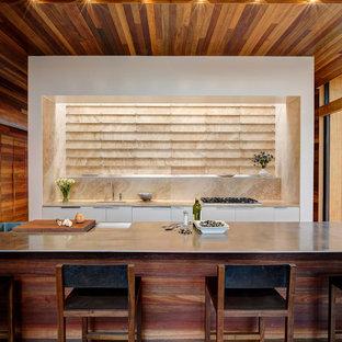 Пример оригинального дизайна: параллельная кухня в современном стиле с столешницей из нержавеющей стали, плоскими фасадами, белыми фасадами, врезной раковиной и фартуком из травертина