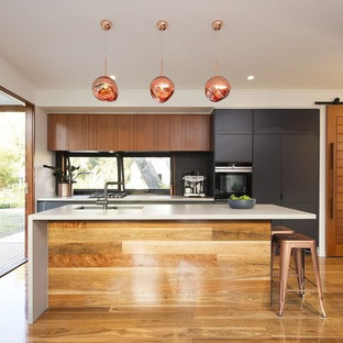 Photo of a contemporary kitchen in Brisbane with an undermount sink, flat-panel cabinets, black cabinets, quartz benchtops, black splashback, mosaic tile splashback, black appliances, medium hardwood floors, with island, brown floor and white benchtop.