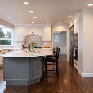 Große Klassische Wohnküche in U-Form mit Triple-Waschtisch, Schrankfronten im Shaker-Stil, grauen Schränken, Quarzwerkstein-Arbeitsplatte, Küchenrückwand in Beige, Rückwand aus Keramikfliesen, Küchengeräten aus Edelstahl, dunklem Holzboden, Kücheninsel, braunem Boden und weißer Arbeitsplatte in Seattle