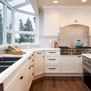 Design ideas for a large traditional u-shaped eat-in kitchen in Seattle with a triple-bowl sink, shaker cabinets, grey cabinets, quartz benchtops, beige splashback, ceramic splashback, stainless steel appliances, dark hardwood floors, with island, brown floor and white benchtop.
