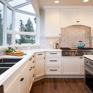 Неиссякаемый источник вдохновения для домашнего уюта: большая п-образная кухня в классическом стиле с обеденным столом, тройной раковиной, фасадами в стиле шейкер, серыми фасадами, столешницей из кварцевого композита, бежевым фартуком, фартуком из керамической плитки, техникой из нержавеющей стали, темным паркетным полом, островом, коричневым полом и белой столешницей