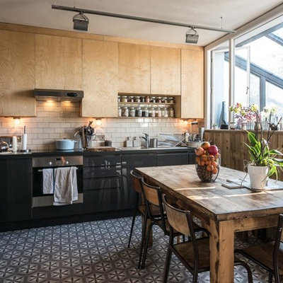 Inspiration for a contemporary l-shaped eat-in kitchen remodel in Sussex with flat-panel cabinets, beige backsplash, subway tile backsplash, stainless steel appliances and no island