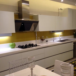 Photo of a large galley separate kitchen in Other with an integrated sink, flat-panel cabinets, white cabinets, solid surface benchtops, orange splashback, glass tile splashback, marble floors and no island.