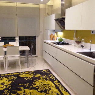 Design ideas for a large modern galley separate kitchen in Other with an integrated sink, flat-panel cabinets, white cabinets, solid surface benchtops, orange splashback, glass tile splashback, marble floors and no island.