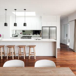 Idéer för mellanstora funkis linjära vitt kök och matrum, med luckor med upphöjd panel, vita skåp, bänkskiva i kvarts, spegel som stänkskydd, en köksö, en undermonterad diskho, stänkskydd med metallisk yta, rostfria vitvaror, mörkt trägolv och brunt golv