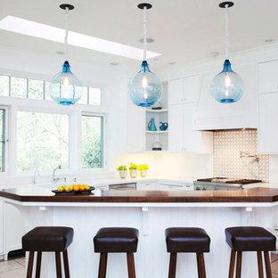 Foto på ett stort vintage kök, med en rustik diskho, skåp i shakerstil, vita skåp, träbänkskiva, flerfärgad stänkskydd, integrerade vitvaror, skiffergolv och en köksö