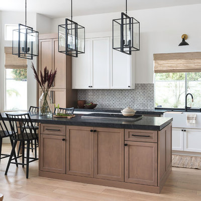 Mid-sized transitional l-shaped light wood floor eat-in kitchen photo in San Diego with a farmhouse sink, shaker cabinets, light wood cabinets, granite countertops, beige backsplash, terra-cotta backsplash, stainless steel appliances, an island and black countertops