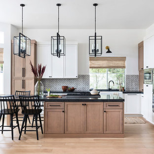 Inspiration for a medium sized traditional l-shaped kitchen/diner in San Diego with a belfast sink, shaker cabinets, granite worktops, terracotta splashback, stainless steel appliances, an island, brown floors, black worktops, medium wood cabinets, grey splashback and medium hardwood flooring.
