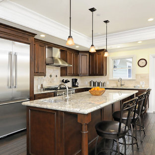Traditional kitchen inspiration - Elegant l-shaped kitchen photo in San Francisco with stainless steel appliances, raised-panel cabinets, dark wood cabinets and granite countertops