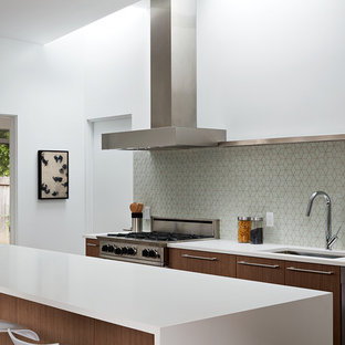 Inspiration for a mid-sized midcentury galley eat-in kitchen in San Francisco with an undermount sink, flat-panel cabinets, dark wood cabinets, green splashback, stainless steel appliances, with island, porcelain floors and brown floor.