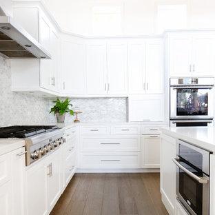 オレンジカウンティの大きいビーチスタイルのおしゃれなキッチン (ドロップインシンク、シェーカースタイル扉のキャビネット、白いキャビネット、クオーツストーンカウンター、グレーのキッチンパネル、モザイクタイルのキッチンパネル、シルバーの調理設備の、濃色無垢フローリング) の写真