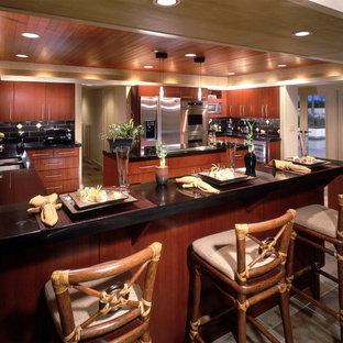This is an example of a tropical kitchen in Orange County with flat-panel cabinets, dark wood cabinets, granite benchtops, black splashback, slate splashback and slate floors.