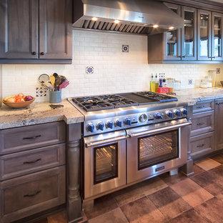 オレンジカウンティの大きいトラディショナルスタイルのおしゃれなキッチン (シェーカースタイル扉のキャビネット、中間色木目調キャビネット、御影石カウンター、白いキッチンパネル、サブウェイタイルのキッチンパネル、シルバーの調理設備の、テラコッタタイルの床、アイランドなし、赤い床) の写真