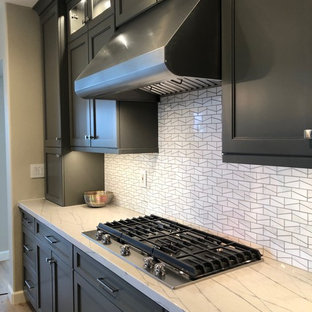 Design ideas for a large contemporary l-shaped eat-in kitchen in Orange County with an undermount sink, recessed-panel cabinets, grey cabinets, quartzite benchtops, white splashback, mosaic tile splashback, stainless steel appliances, vinyl floors, with island, beige floor and white benchtop.