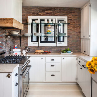Photo of an eclectic u-shaped separate kitchen in Orange County with marble benchtops, a farmhouse sink, white cabinets, stainless steel appliances, multi-coloured splashback and beige benchtop.