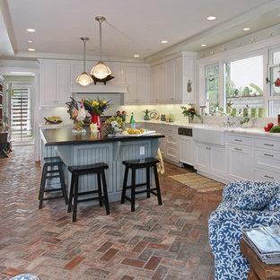 Imagen de cocina costera con fregadero sobremueble y suelo de ladrillo