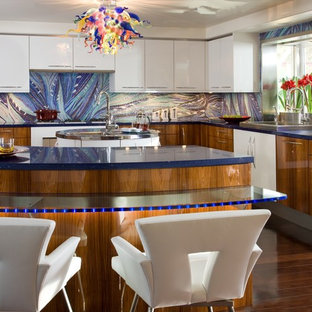 This is an example of a contemporary l-shaped kitchen in San Diego with mosaic tile splashback, glass benchtops, blue splashback, a drop-in sink, flat-panel cabinets, white cabinets, stainless steel appliances and blue benchtop.