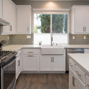 Mid-sized modern u-shaped kitchen in San Diego with a farmhouse sink, shaker cabinets, white cabinets, quartz benchtops, grey splashback, subway tile splashback, stainless steel appliances, plywood floors and with island.