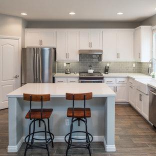 Идея дизайна: п-образная кухня среднего размера в стиле модернизм с раковиной в стиле кантри, фасадами в стиле шейкер, белыми фасадами, столешницей из кварцевого агломерата, серым фартуком, фартуком из плитки кабанчик, техникой из нержавеющей стали, полом из фанеры и островом