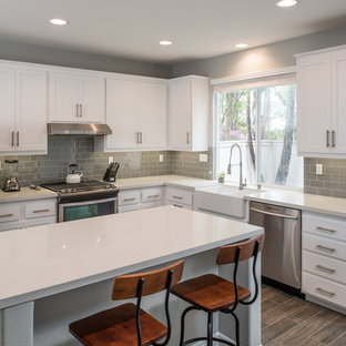 Design ideas for a medium sized modern u-shaped kitchen in San Diego with a belfast sink, shaker cabinets, white cabinets, engineered stone countertops, grey splashback, metro tiled splashback, stainless steel appliances, plywood flooring and an island.