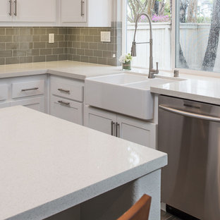 This is an example of a medium sized modern u-shaped kitchen in San Diego with a belfast sink, shaker cabinets, white cabinets, engineered stone countertops, grey splashback, metro tiled splashback, stainless steel appliances, plywood flooring and an island.