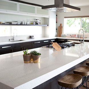 Contemporary eat-in kitchen ideas - Example of a trendy medium tone wood floor eat-in kitchen design in San Diego with a drop-in sink, glass-front cabinets, stainless steel cabinets, quartz countertops, white backsplash, stainless steel appliances and an island