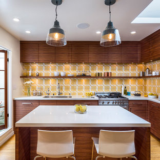 Contemporary kitchen inspiration - Example of a trendy l-shaped light wood floor and yellow floor kitchen design in San Francisco with an undermount sink, flat-panel cabinets, dark wood cabinets, yellow backsplash, stainless steel appliances and an island