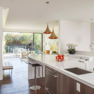 Photo of a large contemporary u-shaped open plan kitchen in San Francisco with a submerged sink, flat-panel cabinets, stainless steel appliances, an island, dark hardwood flooring, white cabinets, engineered stone countertops, white splashback, stone slab splashback and brown floors.