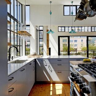 サンフランシスコのモダンスタイルのおしゃれなII型キッチン (フラットパネル扉のキャビネット、パネルと同色の調理設備、大理石カウンター、青いキャビネット) の写真
