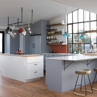 Inspiration for a modern l-shaped open plan kitchen in San Francisco with marble worktops, flat-panel cabinets, blue cabinets, red splashback, ceramic splashback and integrated appliances.