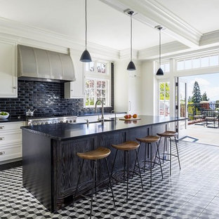 Design ideas for a traditional l-shaped kitchen in New York with a farmhouse sink, recessed-panel cabinets, white cabinets, black splashback, subway tile splashback, panelled appliances, porcelain floors, with island and multi-coloured floor.