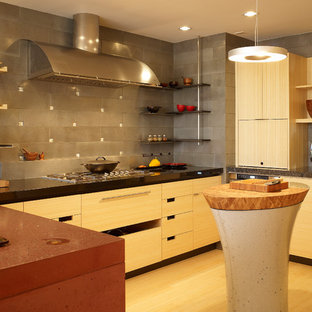 Photo of a mid-sized contemporary u-shaped eat-in kitchen in San Francisco with an undermount sink, flat-panel cabinets, light wood cabinets, concrete benchtops, grey splashback, ceramic splashback, stainless steel appliances and bamboo floors.