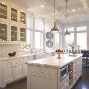 На фото: кухни в классическом стиле с фартуком из плитки кабанчик, раковиной в стиле кантри, стеклянными фасадами, белыми фасадами, белым фартуком, обеденным столом и мраморной столешницей