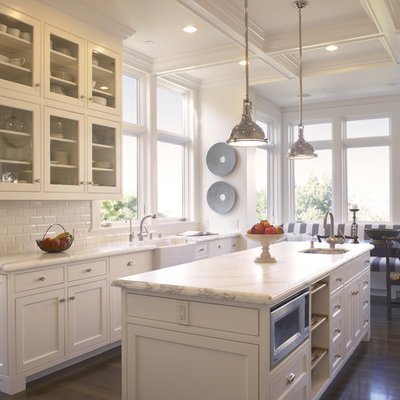 Example of a classic eat-in kitchen design in San Francisco with subway tile backsplash, a farmhouse sink, glass-front cabinets, white cabinets, white backsplash and marble countertops