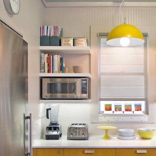 Idéer för ett avskilt, mellanstort modernt l-kök, med rostfria vitvaror, släta luckor, bänkskiva i kvarts, en undermonterad diskho, skåp i ljust trä, vitt stänkskydd och laminatgolv