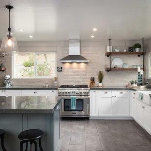 Exemple d'une cuisine nature en L de taille moyenne avec un évier de ferme, des portes de placard blanches, un plan de travail en granite, une crédence grise, une crédence en brique, un électroménager en acier inoxydable, un sol en carreaux de ciment, un îlot central, un sol gris et un plan de travail gris.