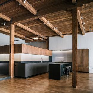 Zweizeilige Industrial Wohnküche mit flächenbündigen Schrankfronten, hellbraunen Holzschränken, Küchenrückwand in Schwarz und Elektrogeräten mit Frontblende in San Francisco