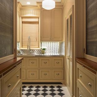 Immagine di una cucina a L chic con lavello integrato, ante con riquadro incassato, ante beige, top in acciaio inossidabile, paraspruzzi grigio, paraspruzzi con piastrelle di metallo, pavimento multicolore e top grigio