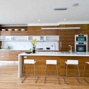 Modelo de cocina lineal, minimalista, de tamaño medio, abierta, con armarios con paneles lisos, puertas de armario de madera oscura, salpicadero blanco, electrodomésticos de acero inoxidable, fregadero de un seno, suelo de madera clara y una isla