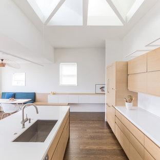 Foto di una cucina ad ambiente unico moderna di medie dimensioni con lavello sottopiano, ante lisce, ante in legno chiaro, top in pietra calcarea, paraspruzzi bianco, paraspruzzi in lastra di pietra, elettrodomestici da incasso, parquet scuro e isola