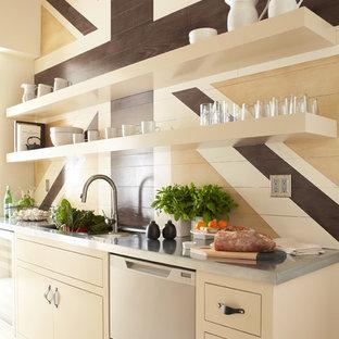 Immagine di una cucina minimal con lavello sottopiano, ante lisce, ante beige, elettrodomestici in acciaio inossidabile e top in zinco